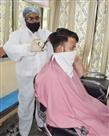 पीपीई किट पहन काट रहे ग्राहकों के बाल