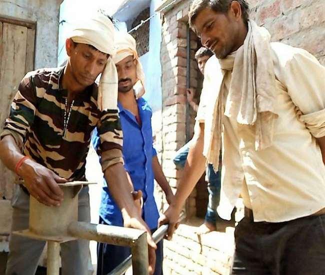 अलीगढ़ में खराब हैंडपंप को सुधारते कर्मचारी।