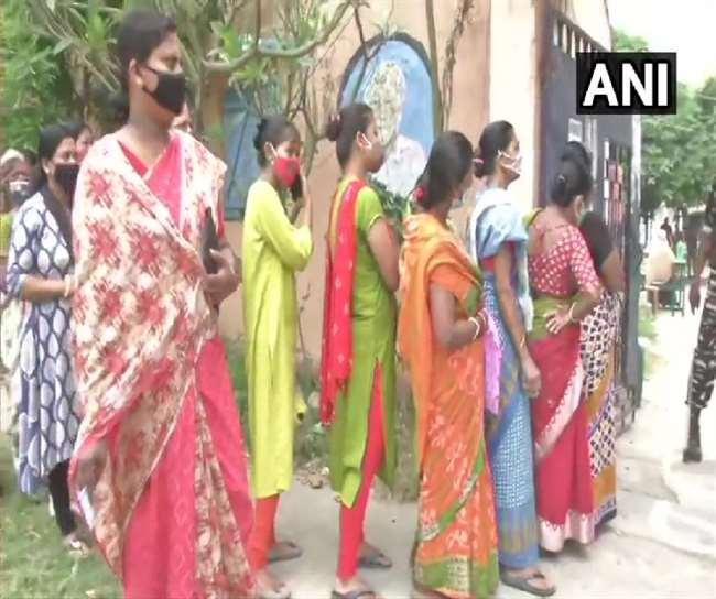 मतदान केंद्र पर वोट डालने के लिए लाइन पर लगी महिलाएं