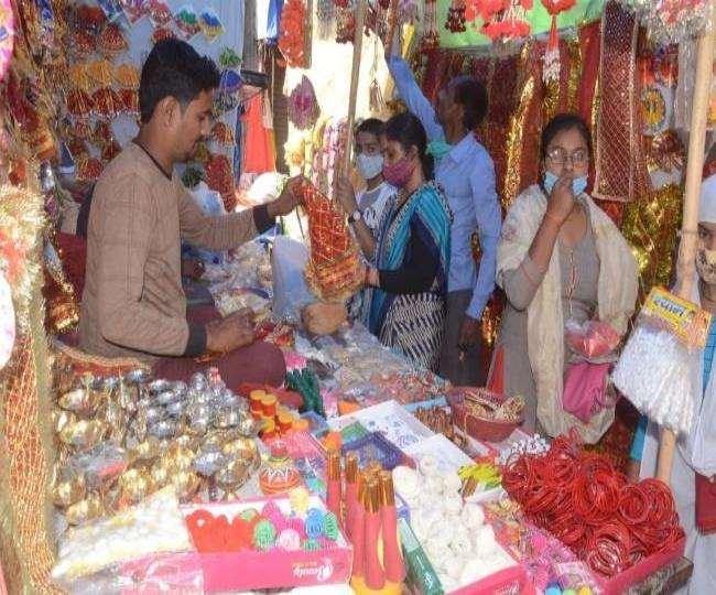 बाजार में मास्क पहने श्रद्धालु मां दुर्गा की मूर्तियों की खरीदारी करने पहुंच रहे हैं।