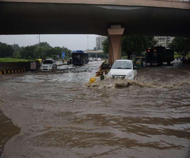 एम्स फ्लाईओवर के नीचे भरे पानी से गुजरते वाहन सवार।
