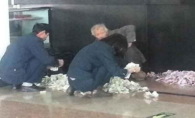 पोस्ट ऑफिस में जमीन पर नोट बिछाकर गिनने वाले इस भिखारी की फोटो हुई वायरल